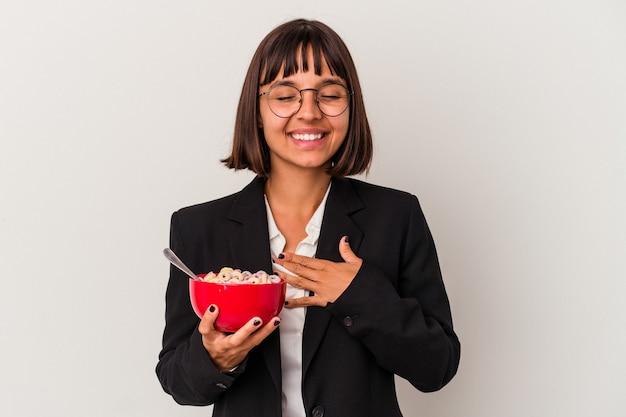 Jonge gemengd ras zakenvrouw die granen eet die op een witte achtergrond wordt geïsoleerd lacht hardop terwijl ze de hand op de borst houdt.