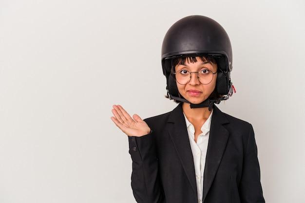 Jonge gemengd ras zakenvrouw draagt een motorhelm geïsoleerd met een kopie ruimte op een handpalm en houdt een andere hand op de taille.