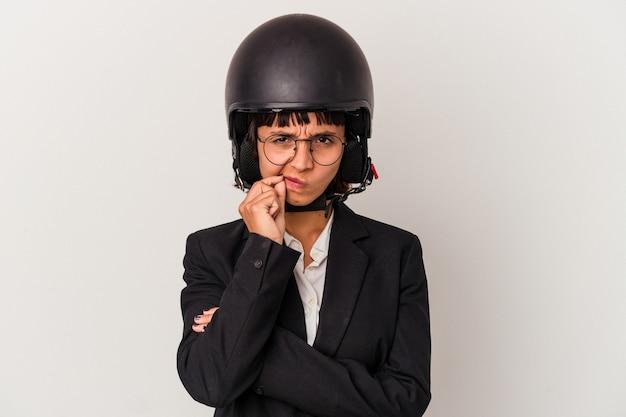 Jonge gemengd ras zakenvrouw draagt een motorhelm geïsoleerd met vingers op lippen die een geheim houden.