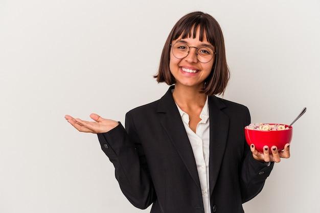 Jonge gemengd ras zakenvrouw eten granen geïsoleerd op een witte achtergrond met een kopie ruimte op een palm en met een andere hand op de taille.