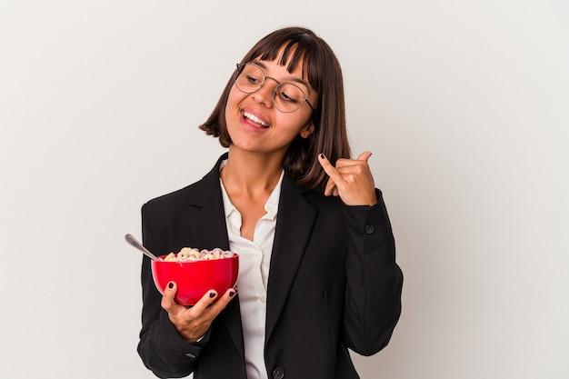 Jonge gemengd ras zakenvrouw eten granen geïsoleerd op een witte achtergrond met een mobiel telefoongesprek gebaar met vingers.