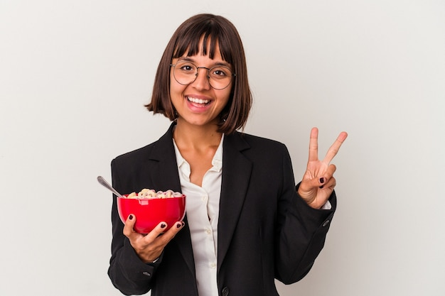 Jonge gemengd ras zakenvrouw eten granen geïsoleerd op een witte achtergrond met nummer twee met vingers.
