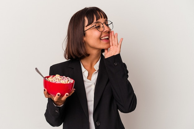 Jonge gemengd ras zakenvrouw eten granen geïsoleerd op een witte achtergrond schreeuwen en houden palm in de buurt van geopende mond.
