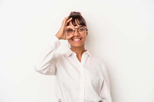 Jonge gemengd ras zakenvrouw geïsoleerd op een witte achtergrond opgewonden houden ok gebaar op oog.