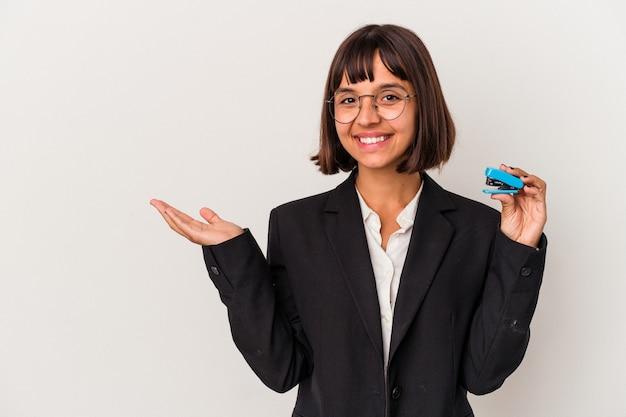 Jonge gemengd ras zakenvrouw met een nietmachine geïsoleerd op een witte achtergrond met een kopie ruimte op een palm en met een andere hand op de taille.