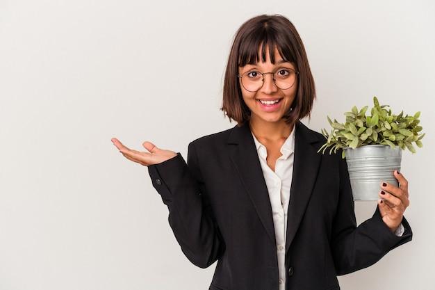Jonge gemengd ras zakenvrouw met een plant geïsoleerd op een witte achtergrond met een kopie ruimte op een palm en met een andere hand op de taille.