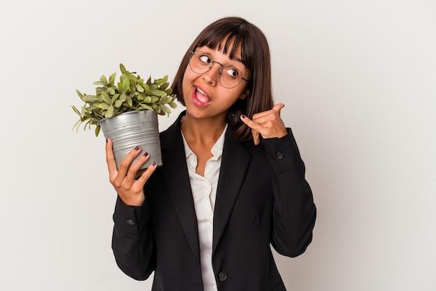 Jonge gemengd ras zakenvrouw met een plant geïsoleerd op een witte achtergrond met een mobiel telefoongesprek gebaar met vingers.