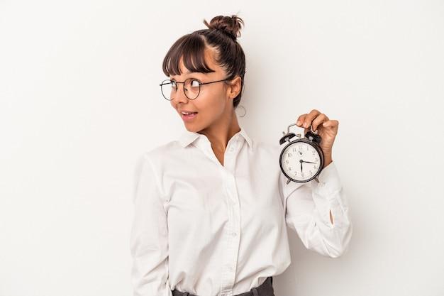 Jonge gemengd ras zakenvrouw met een wekker geïsoleerd op een witte achtergrond kijkt opzij glimlachend, vrolijk en aangenaam.