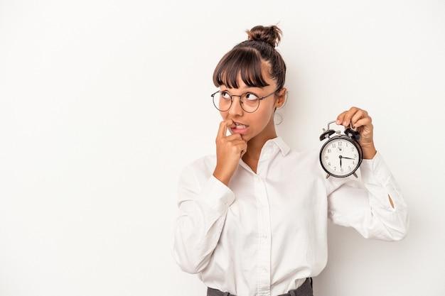 Jonge gemengd ras zakenvrouw met een wekker geïsoleerd op een witte achtergrond ontspannen denken over iets kijken naar een kopie ruimte.