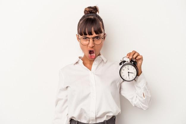 Jonge gemengd ras zakenvrouw met een wekker geïsoleerd op een witte achtergrond schreeuwen erg boos en agressief.