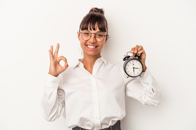 Jonge gemengd ras zakenvrouw met een wekker geïsoleerd op een witte achtergrond vrolijk en zelfverzekerd weergegeven: ok gebaar.