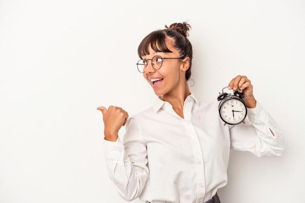 Jonge gemengd ras zakenvrouw met een wekker geïsoleerd op een witte achtergrond wijst met duim vinger weg, lachen en zorgeloos.