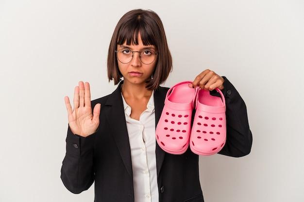 Jonge gemengd ras zakenvrouw met sandalen geïsoleerd op een witte achtergrond permanent met uitgestrekte hand weergegeven: stopbord, voorkomen dat u.