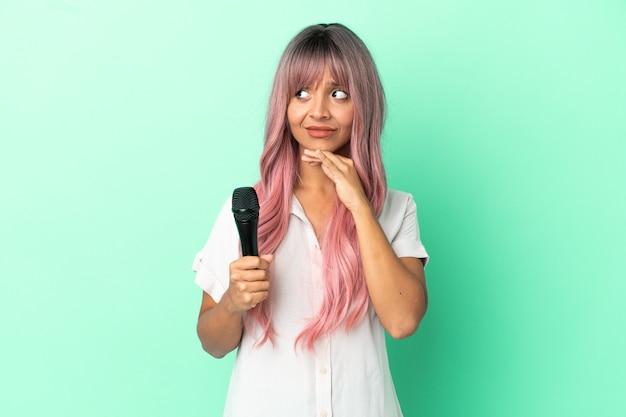 Jonge gemengd ras zanger vrouw met roze haren geïsoleerd op groene achtergrond twijfels