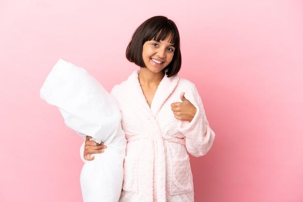 Jonge gemengd ras zwangere vrouw geïsoleerd op roze achtergrond in pyjama en met duimen omhoog omdat er iets goeds is gebeurd