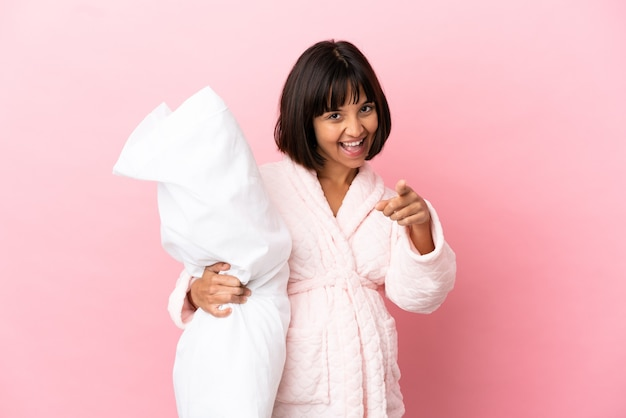 Jonge gemengd ras zwangere vrouw geïsoleerd op roze achtergrond in pyjama en wijst vinger naar je met een zelfverzekerde uitdrukking
