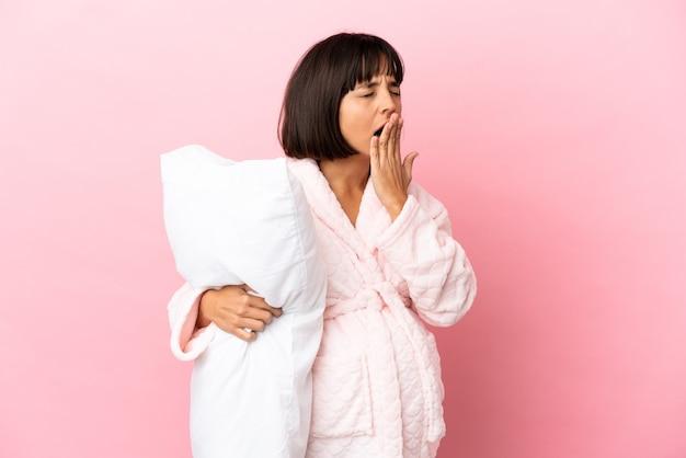 Jonge gemengd ras zwangere vrouw geïsoleerd op roze muur in pyjama en met een kussen en geeuwen