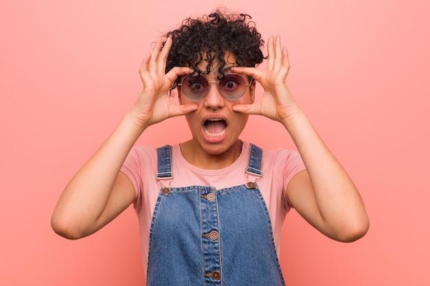 Jonge gemengde afrikaanse amerikaanse tienervrouw die ogen houden geopend om een succeskans te vinden.