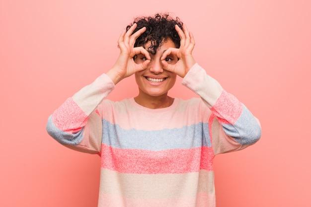 Jonge gemengde afrikaanse amerikaanse tienervrouw die ok teken over ogen tonen