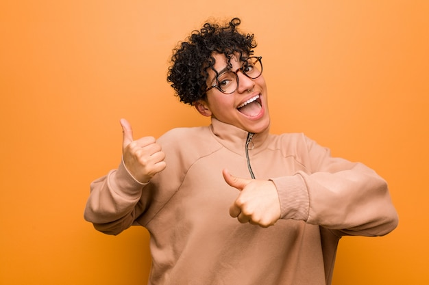 Jonge gemengde afrikaanse amerikaanse vrouw tegen een bruine muur die beide duimen omhoog, glimlachend en zeker opheft.