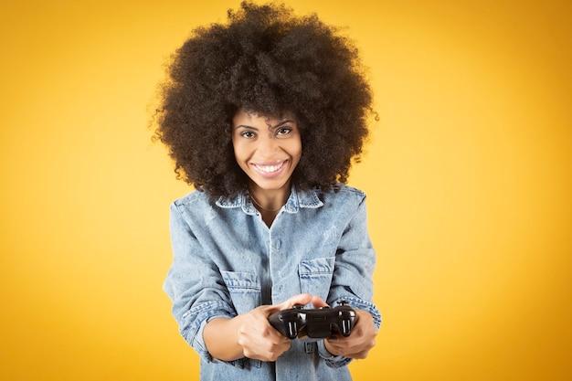 Jonge gemengde afro-amerikaanse vrouw, afro haar, gelukkig, spelen van videogames met spelbesturing, leuk