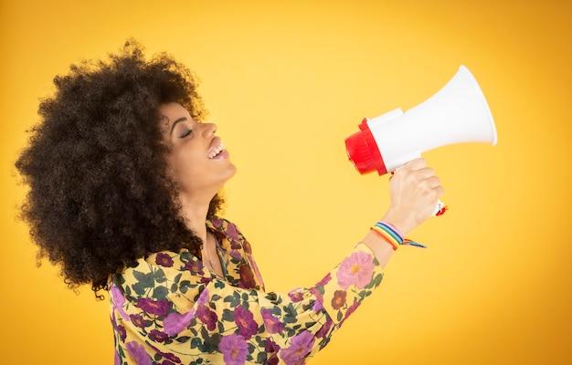 Jonge gemengde afro-amerikaanse vrouw die gay pride-gebeurtenis viert die het symbool van de regenboogvlag van lgbt draagt