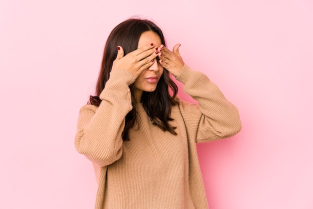 Jonge gemengde geïsoleerde ras spaanse vrouw bang die ogen behandelt met handen.