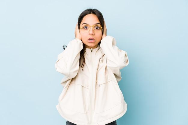 Jonge gemengde geïsoleerde ras spaanse vrouw die oren behandelt met handen die niet te hard geluid proberen te horen.