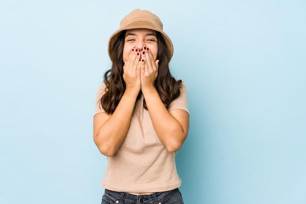 Jonge gemengde geïsoleerde ras spaanse vrouw die over iets lacht, die mond behandelt met handen.