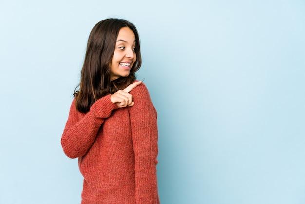Jonge gemengde geïsoleerde ras spaanse vrouw kijkt opzij glimlachend, vrolijk en aangenaam.