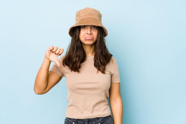 Jonge gemengde geïsoleerde ras spaanse vrouw met duim omlaag, teleurstellingconcept.