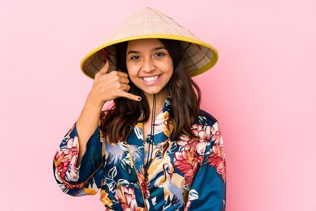 Jonge gemengde geïsoleerde ras spaanse vrouw tonend een mobiel telefoongesprekgebaar met vingers.
