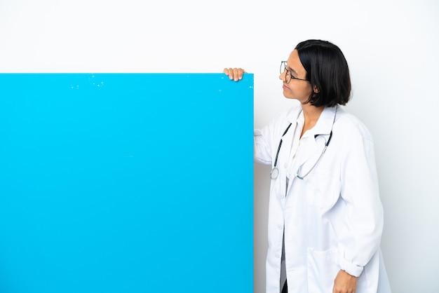 Jonge gemengde race arts vrouw met een groot bordje geïsoleerd op een witte achtergrond in laterale positie