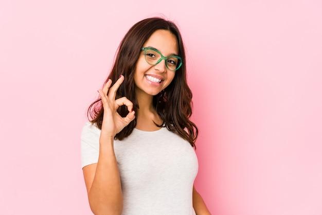 Jonge gemengde race spaanse vrouw geïsoleerd vrolijk en zelfverzekerd tonend ok gebaar.