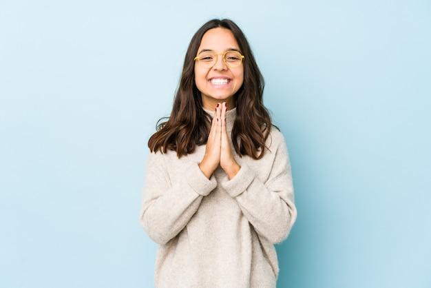 Jonge gemengde race spaanse vrouw geïsoleerde hand in hand bidden in de buurt van de mond, voelt zich zelfverzekerd.