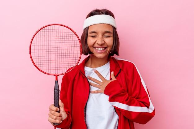 Jonge gemengde race vrouw badminton spelen geïsoleerd op roze muur lacht hardop hand op de borst te houden.