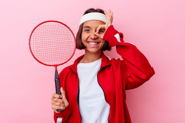 Jonge gemengde race vrouw badminton spelen geïsoleerd op roze muur opgewonden houden ok gebaar op oog.