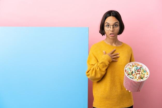 Jonge gemengde race vrouw met popcorn met een grote banner over geïsoleerde achtergrond verrast en geschokt terwijl ze naar rechts kijkt