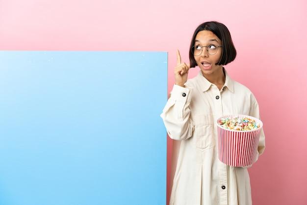 Jonge gemengde race vrouw met popcorns met een grote banner over geïsoleerde achtergrond met de bedoeling de oplossing te realiseren terwijl ze een vinger opheft