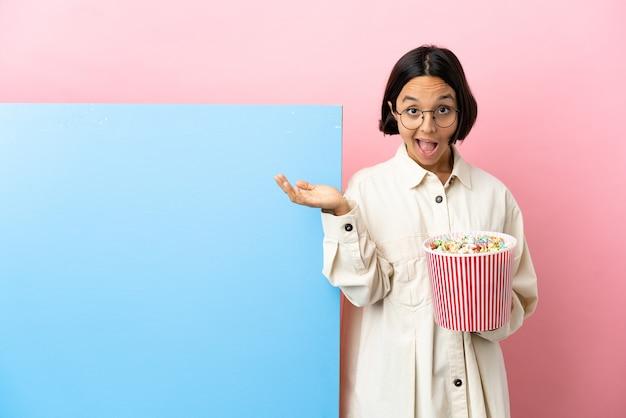 Jonge gemengde race vrouw met popcorns met een grote banner over geïsoleerde achtergrond met geschokte gelaatsuitdrukking