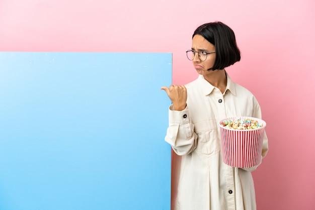 Jonge gemengde race vrouw met popcorns met een grote banner over geïsoleerde achtergrond ongelukkig en naar de zijkant wijzend
