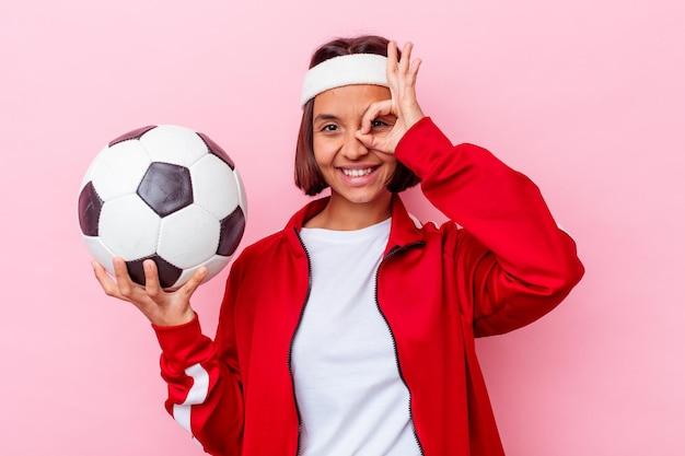 Jonge gemengde race vrouw voetballen geïsoleerd op roze muur opgewonden houden ok gebaar op oog.