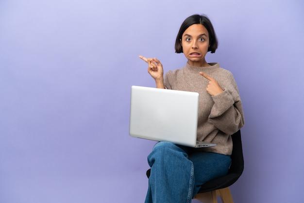 Jonge gemengde race vrouw zittend op een stoel met laptop geïsoleerd op paarse achtergrond bang en wijzend naar de kant