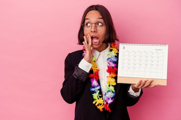Jonge gemengde race zakenvrouw die de dagen telt voor vakanties die op roze muur worden geïsoleerd, zegt een geheim heet remmend nieuws en kijkt opzij