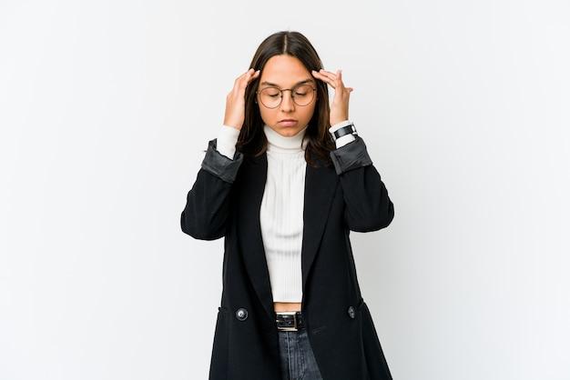 Jonge gemengde race zakenvrouw geïsoleerd op een witte muur tempels aan te raken en hoofdpijn te hebben.