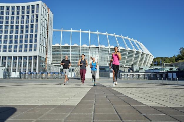 Jonge gemengde raciale atleten die op stadionachtergrond lopen