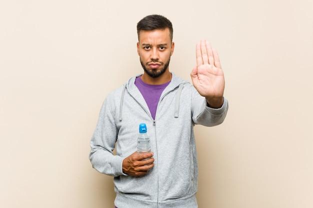 Jonge gemengde ras aziatische mens die een waterfles houden die zich met uitgestrekte hand bevinden die eindeteken tonen, die u verhinderen.