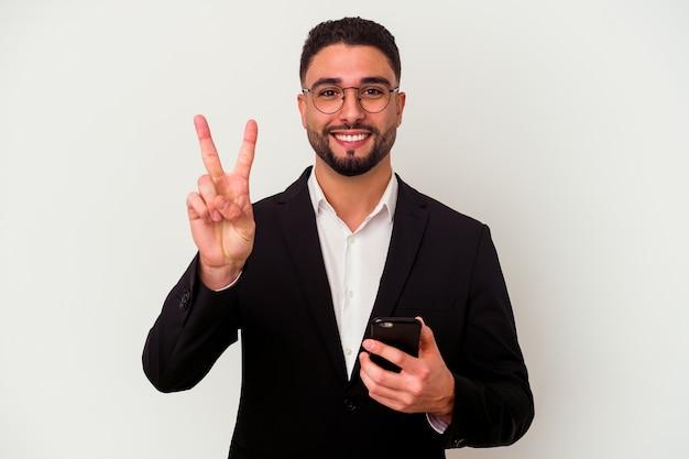 Jonge gemengde ras bedrijfsmens die een mobiele telefoonmens houdt die op witte achtergrond wordt geïsoleerd die nummer twee met vingers toont.