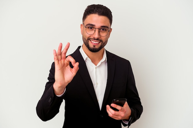 Jonge gemengde ras bedrijfsmens die een mobiele telefoonmens houdt die op witte muur wordt geïsoleerd vrolijk en zeker die ok gebaar toont.