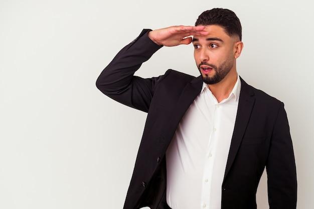 Jonge gemengde ras bedrijfsmens die op witte muur wordt geïsoleerd die ver weg kijkt die hand op voorhoofd houdt.